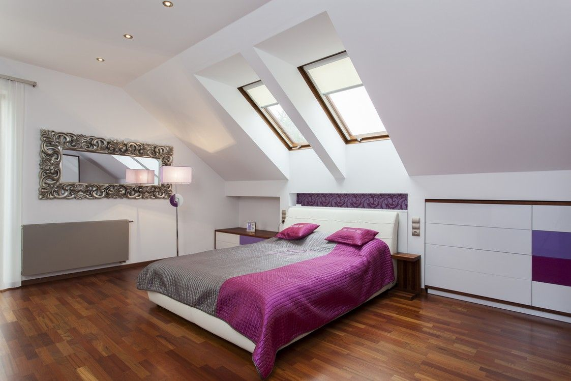 Guest bedroom in attic with skylight and purple accents