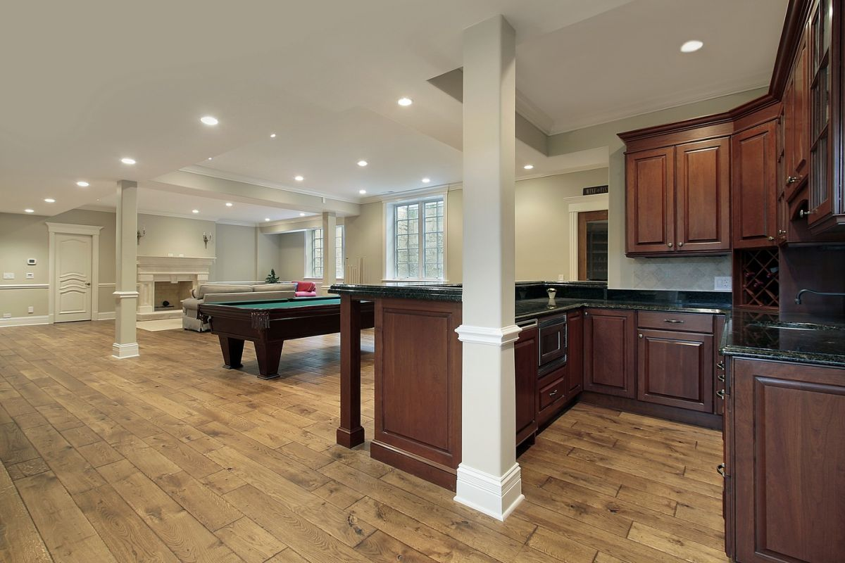 Well-lit basement with full kitchen, pool table and fireplace