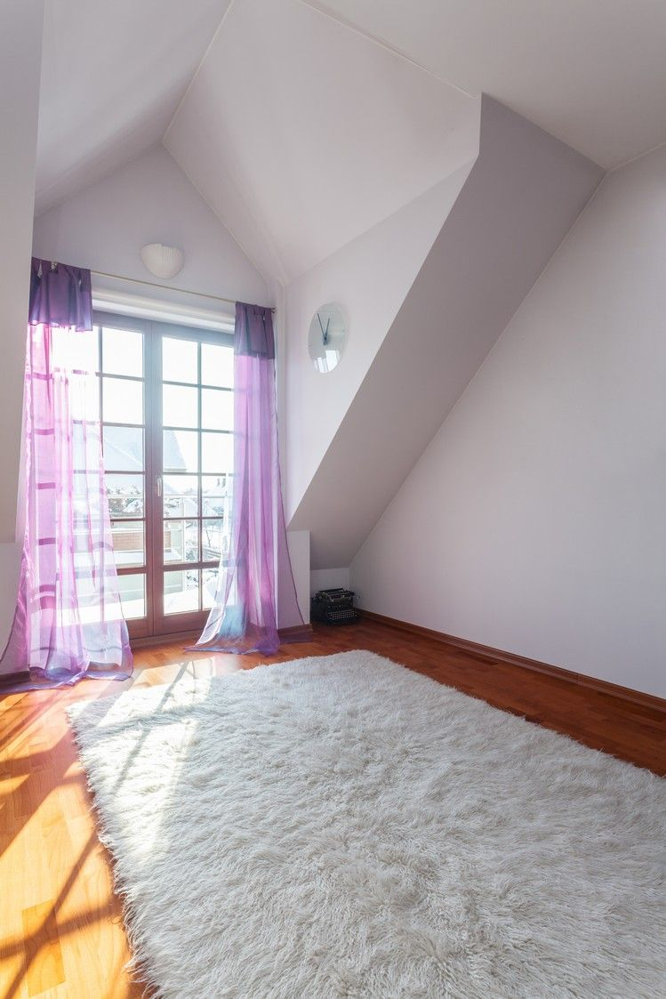 Attic bedroom with windowed doors leading to deck