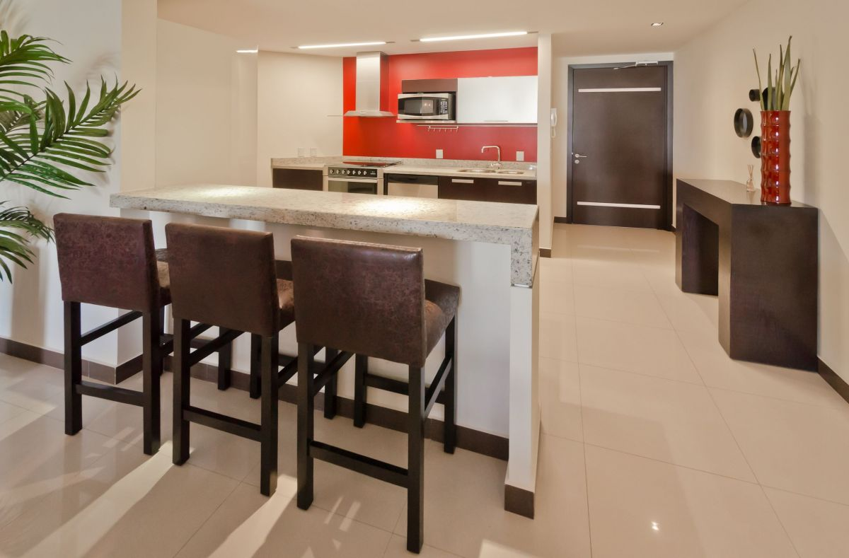 modern kitchen with its own red accent wall leading a dining room countertop table