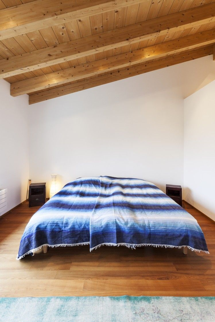 Charming guest bedroom with exposed beams and hardwood floors