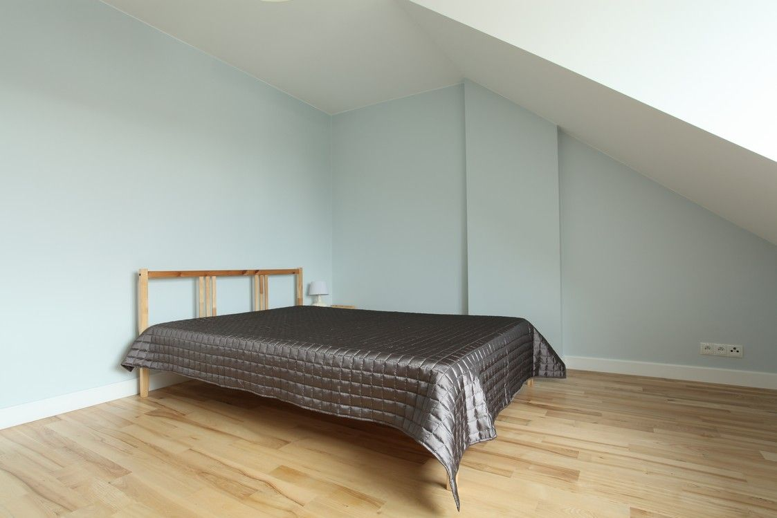 Guest bedroom in attic with fresh hardwood floors and mint walls