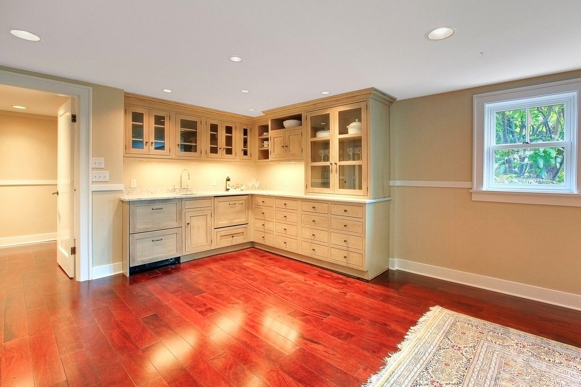 Basement with cherry red wood floor and small kitchen