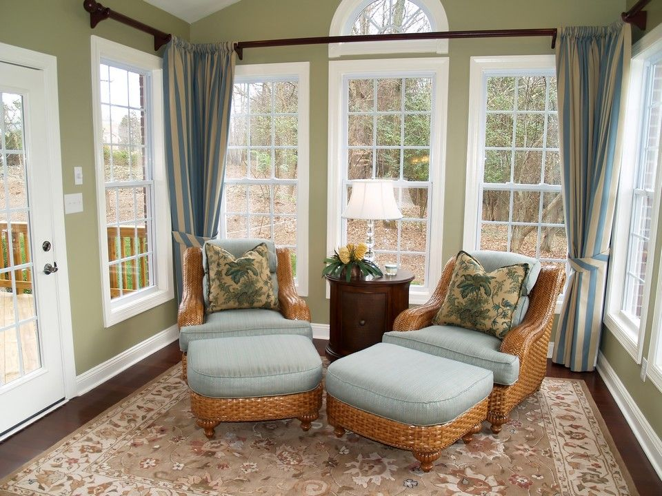 Comfortable wicker chairs in beautiful light green sunroom