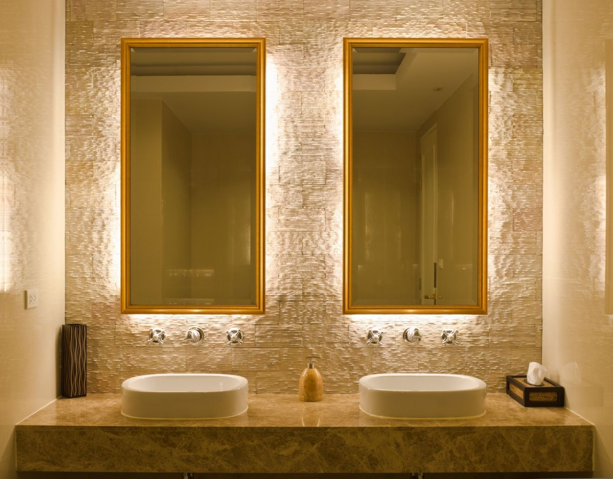 Double sink bathroom with back-lit mirrors on textured stone
