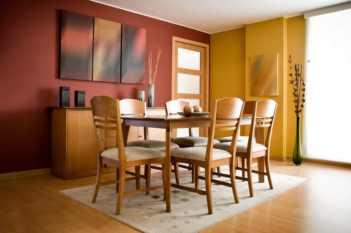 Rich red and yellow walls light up hardwood dining room
