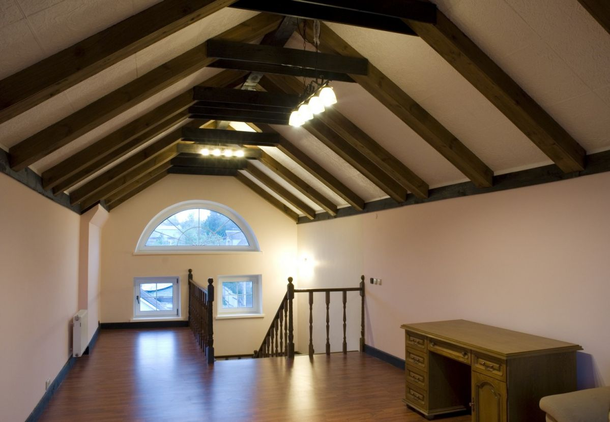 half circle window top relaxing attic space featuring half circle window and exposed wooden beams