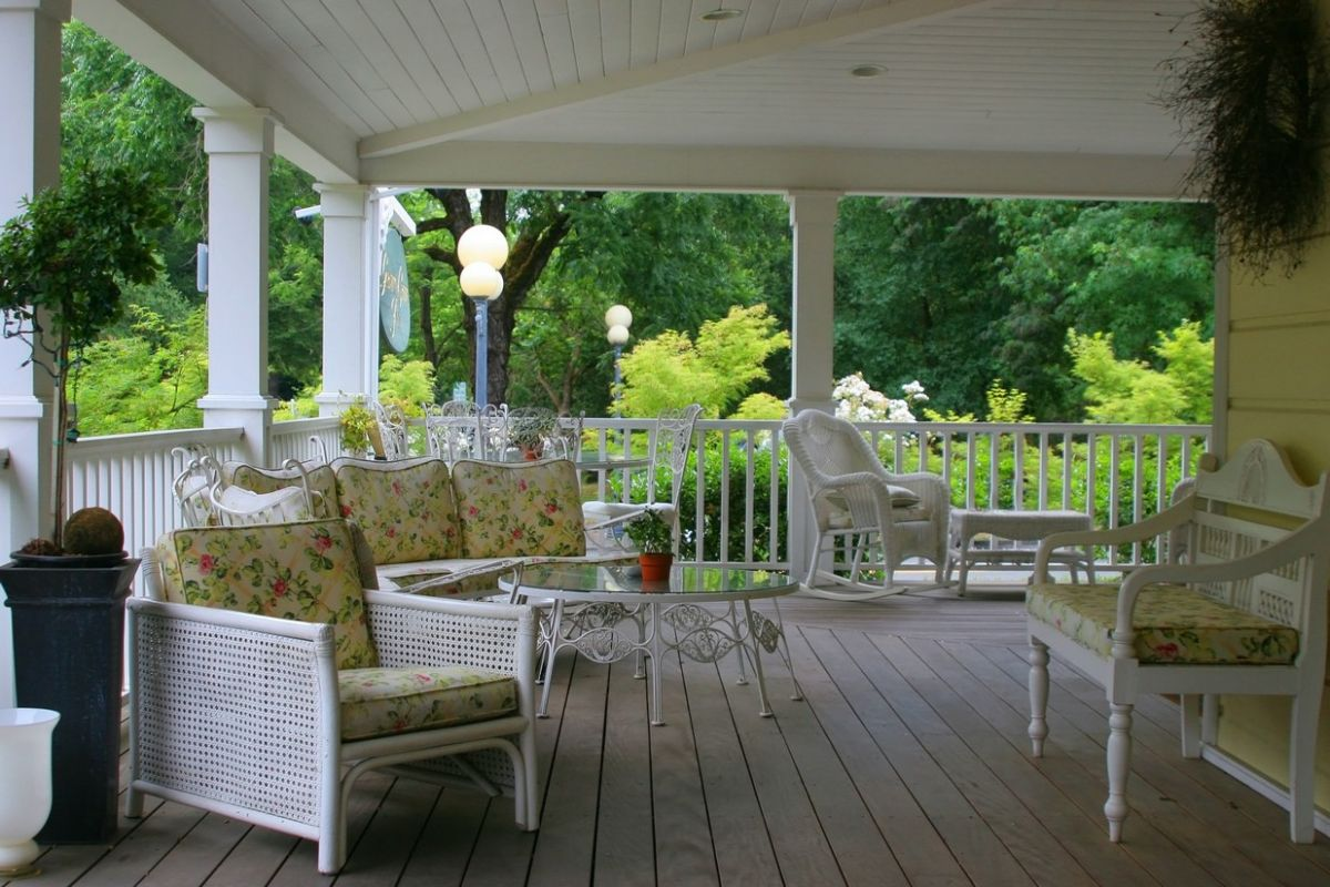 Cape cod style deck with wicker and wooden furniture