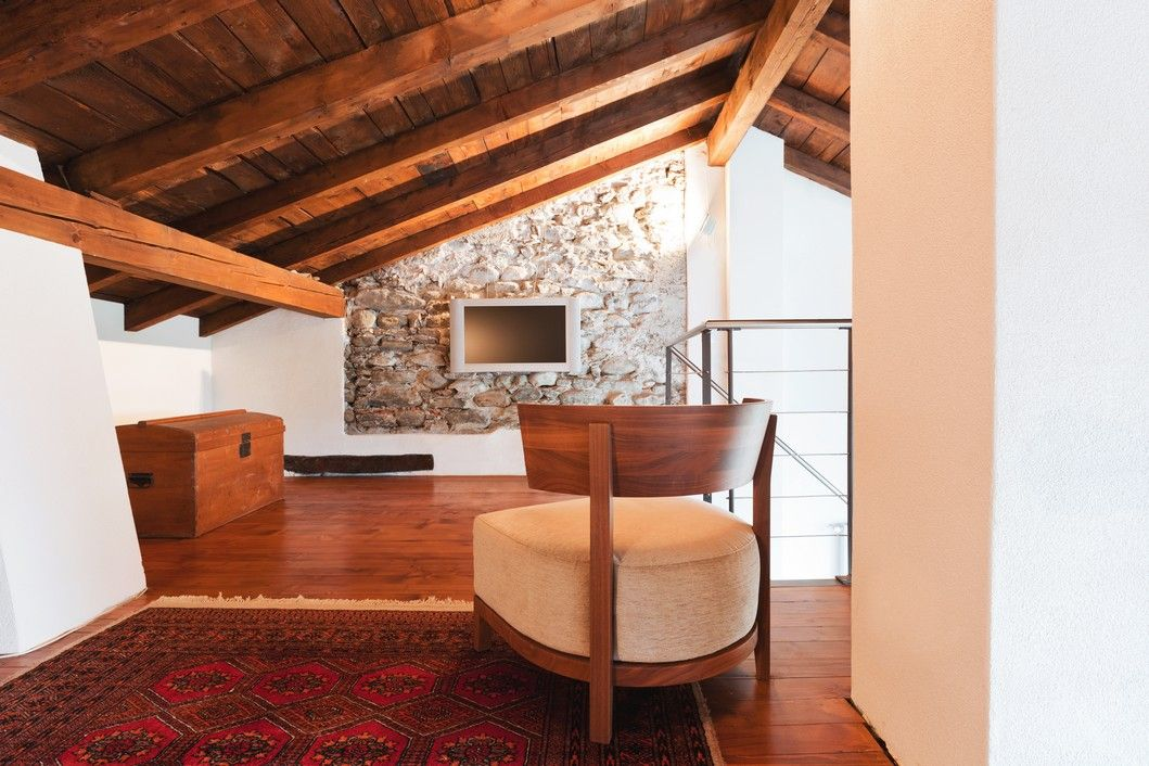Exposed wooden beams, stones make for a rustic entertainment area