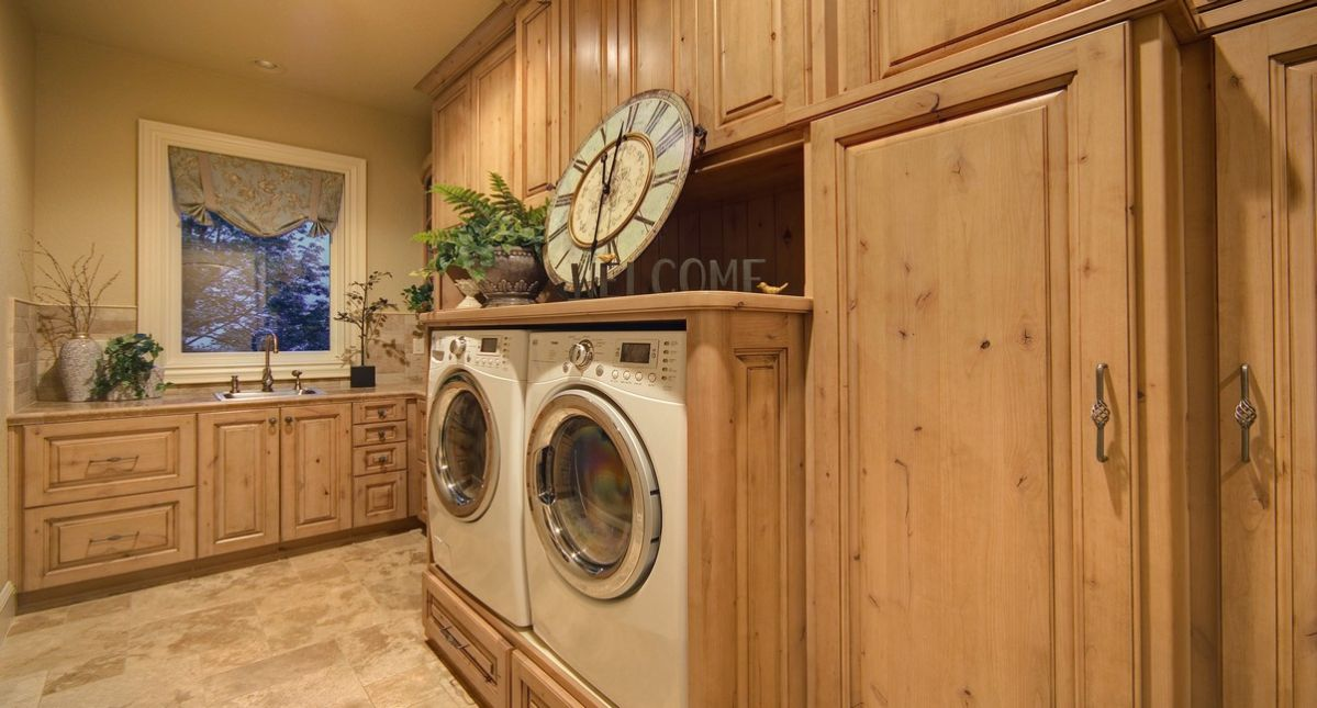 Beautiful laundry room with sink, wood paneling and cabinets