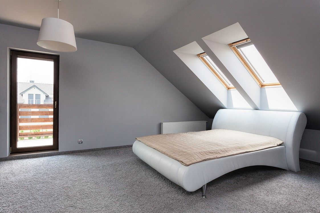 Sleek guest bedroom with modern flair and sky lights in attic