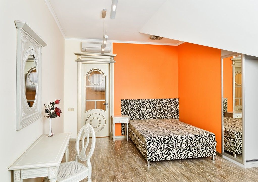 Small bedroom in attic with lovely orange wall perfect for guests