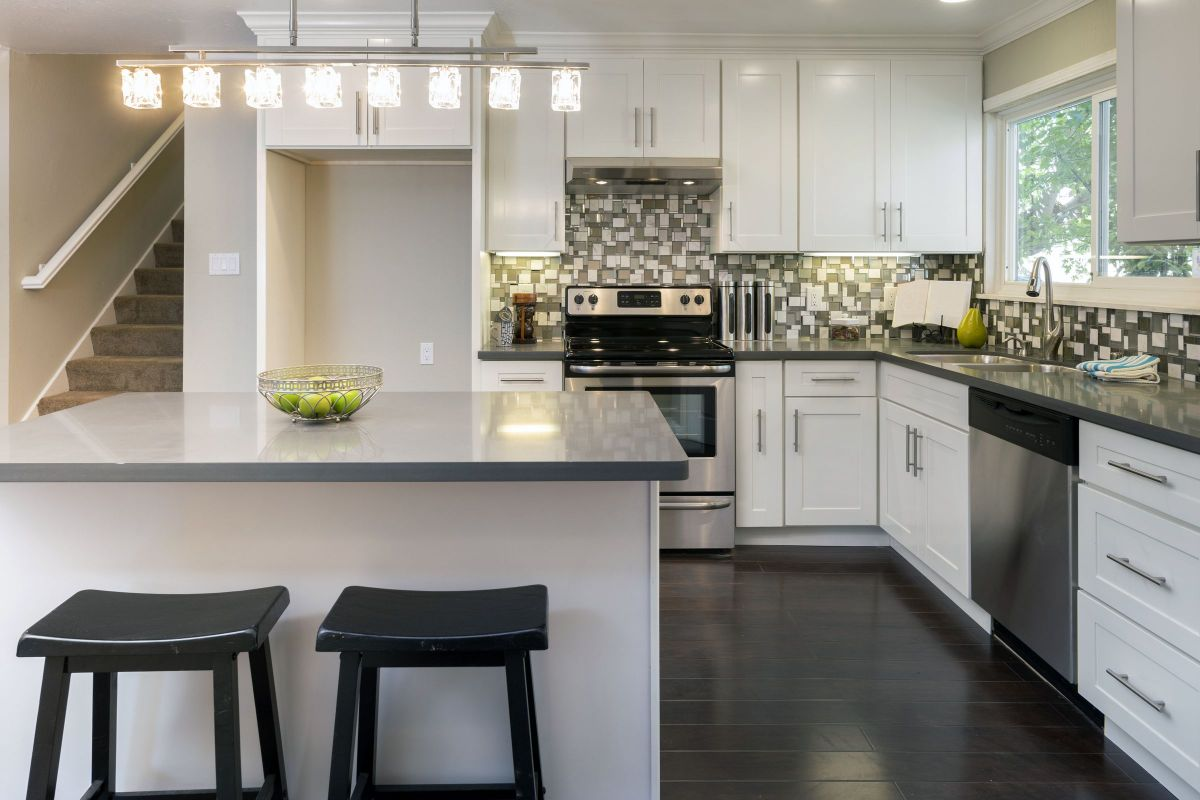 White and Black Custom Kitchen Countertops with Bar Stool Seating and Cabinets