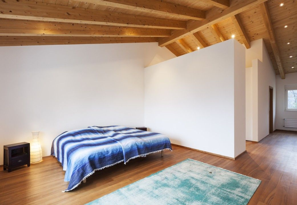 Minimalist bedroom in attic with exposed wooden beams