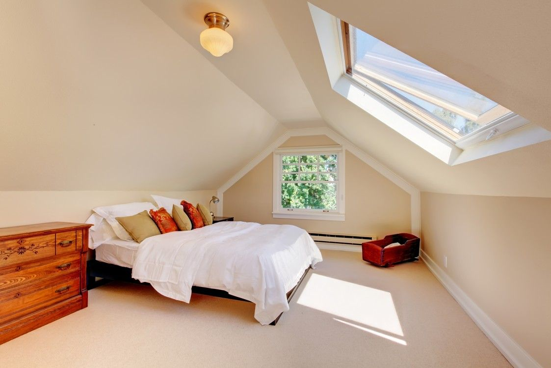 Comfortable and charming bedroom in attic with skylight