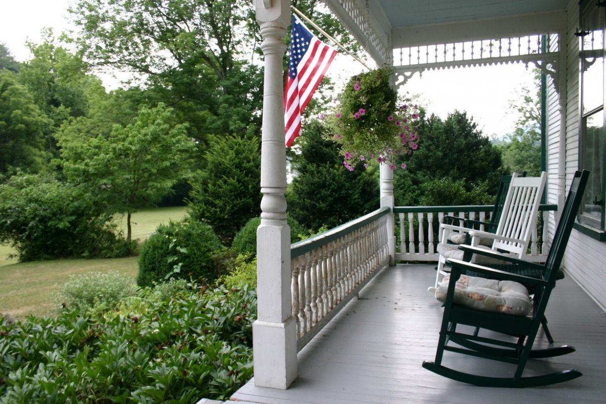 Classic New England porch with rocking chairs and a view of yard