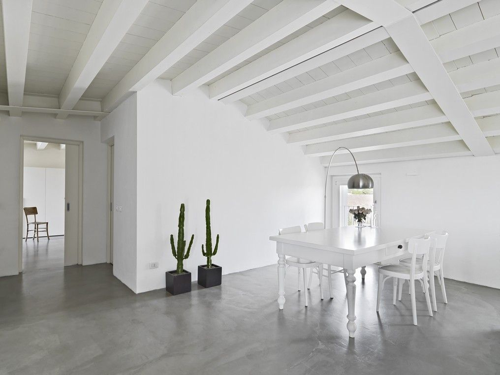 White attic featuring minimalist style and exposed beams