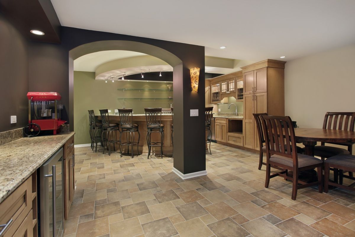 Tiled basement has beautiful color contrast with mini kitchen, bar and eating area