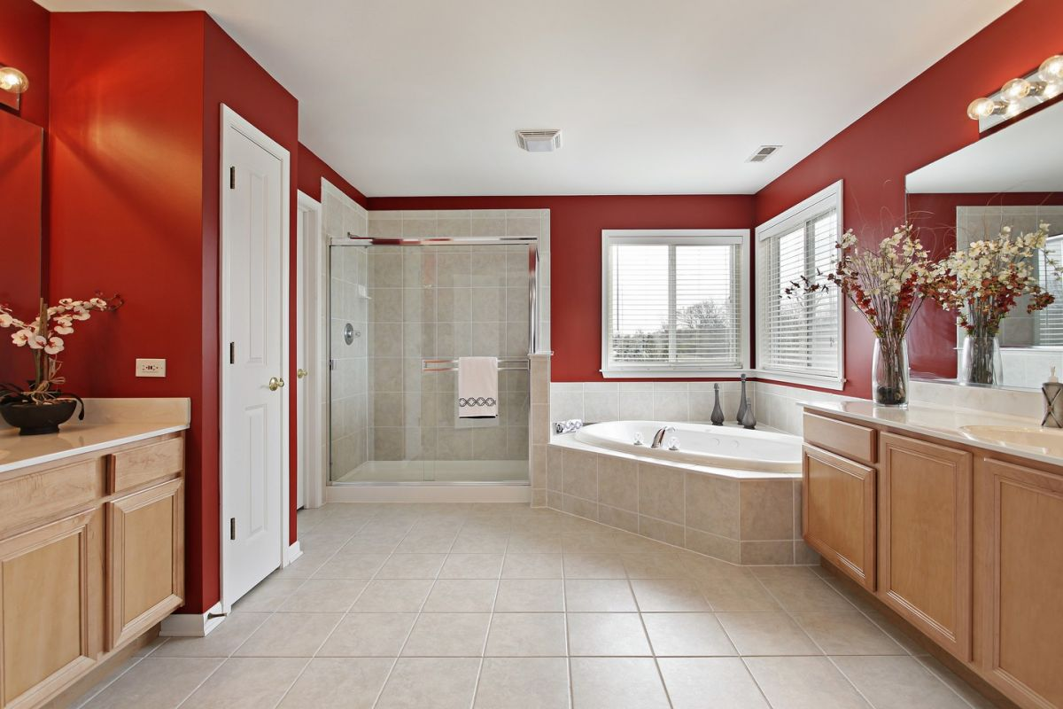 Large bathroom with walk-in shower, jacuzzi and red walls that reflect light beautifully