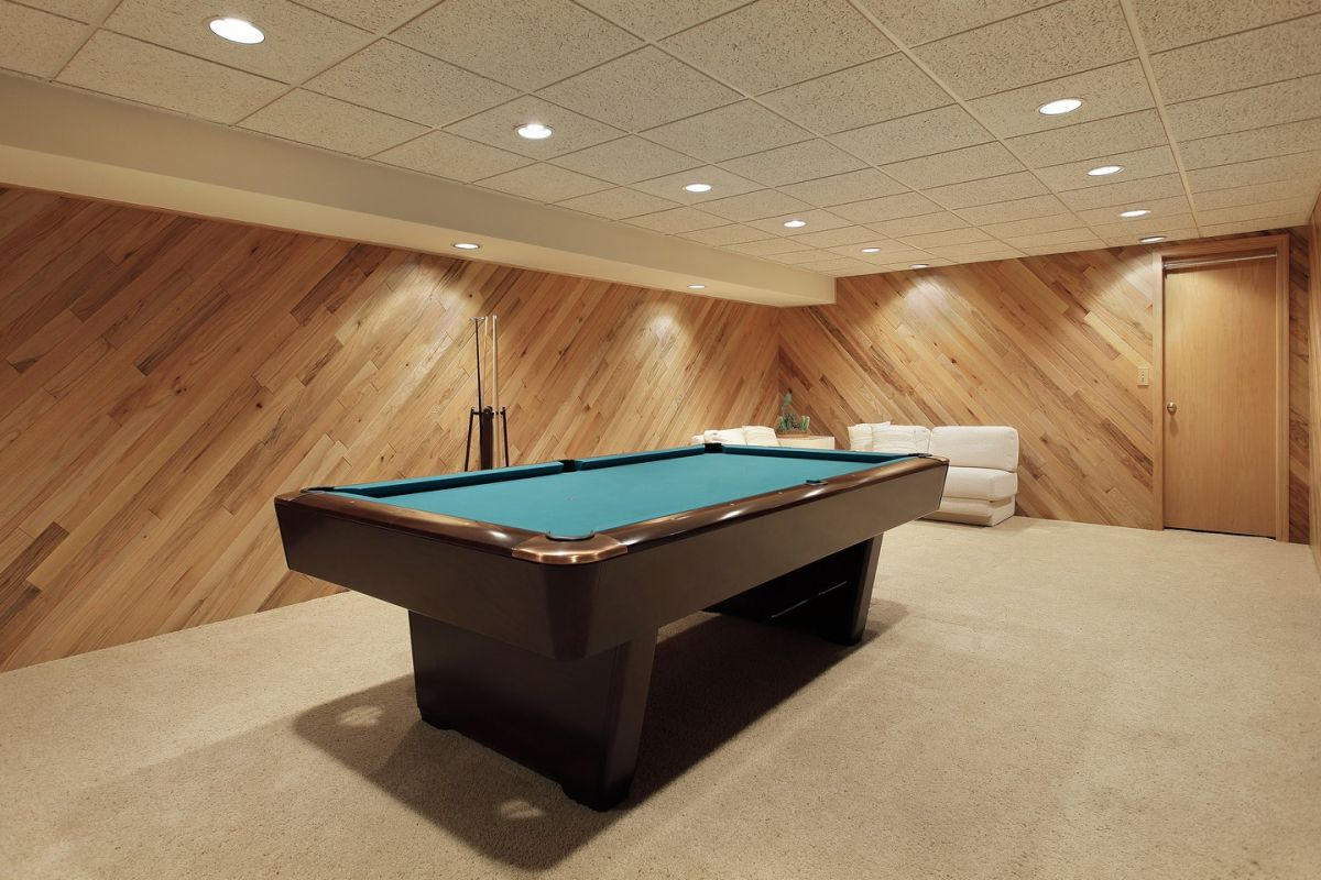 Carpeted Basement With Wood Panel Walls And Pool Table