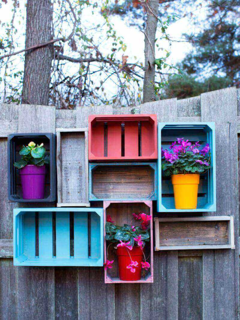 Use wood crates to add storage and color to your fence