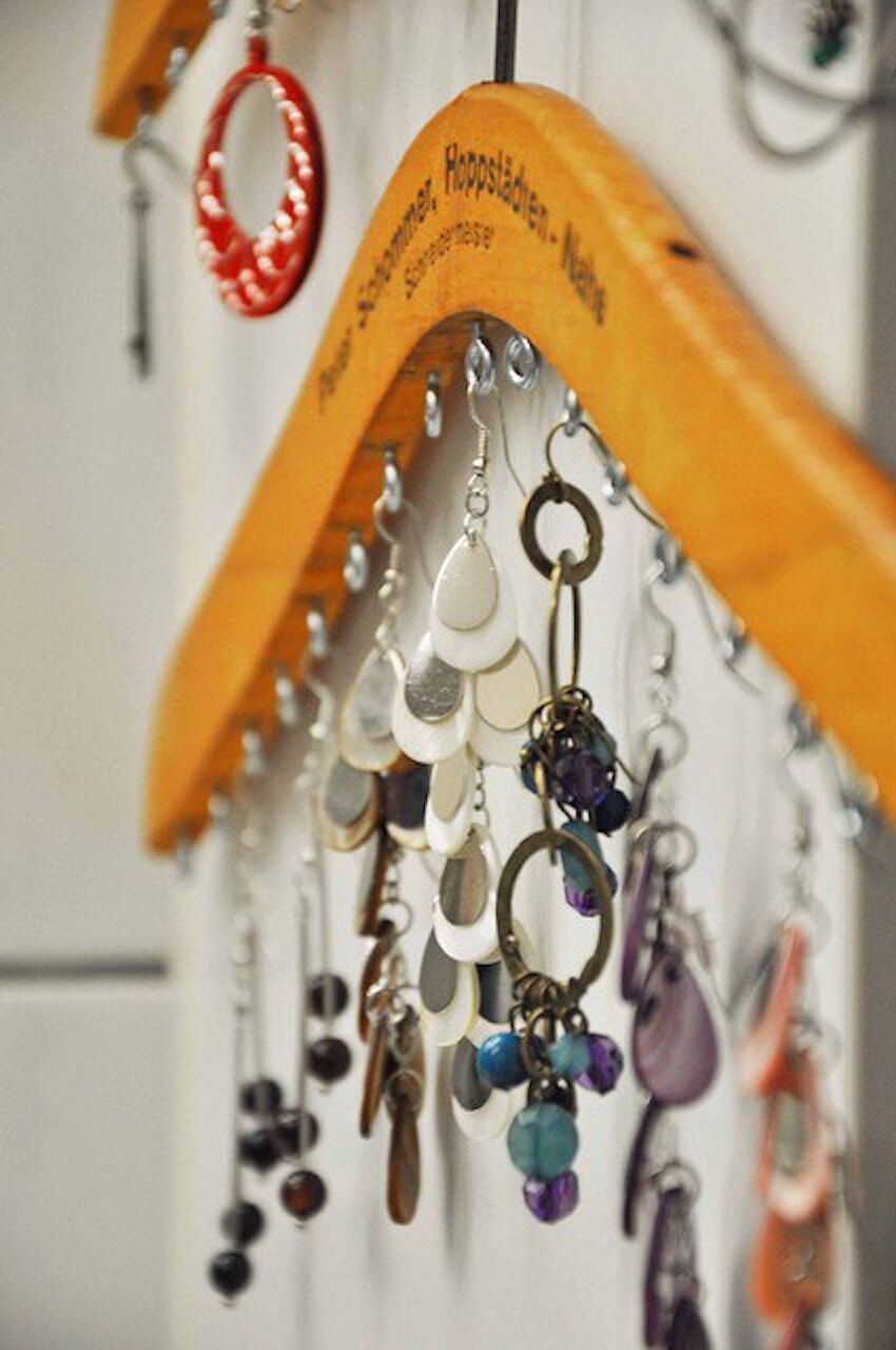 Home interior project: Using hooks and a clothes hanger, you can create a simple and effective DIY jewelry organizer.