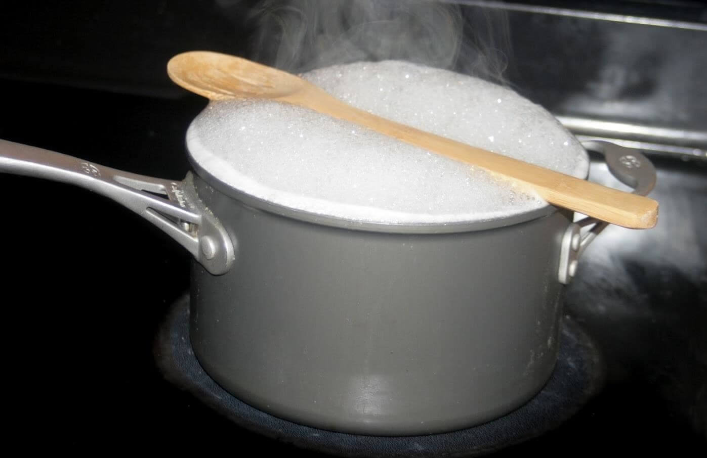 The simple act of putting a wooden spoon over the pot will keep it from boiling over