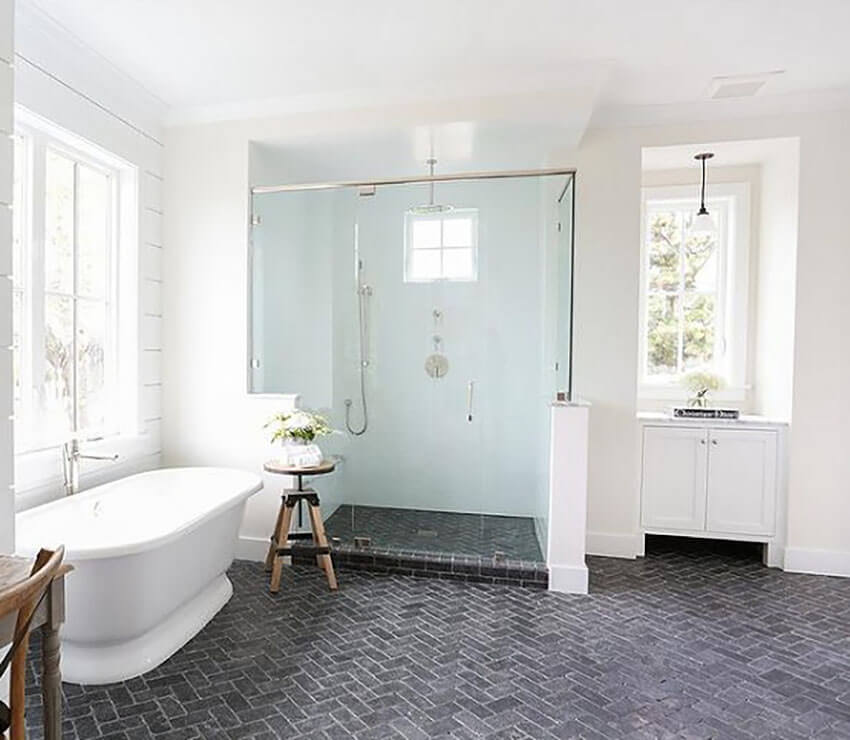 Gray brick floor tile in a herringbone pattern, creating a beautiful contrast to a white bathroom.