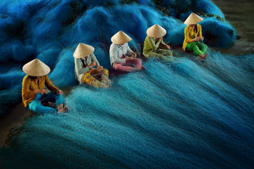 The daily work of women mending nets in Vietnam is full of beauty through the lens of the photographer. Image Source: SIPA Contest