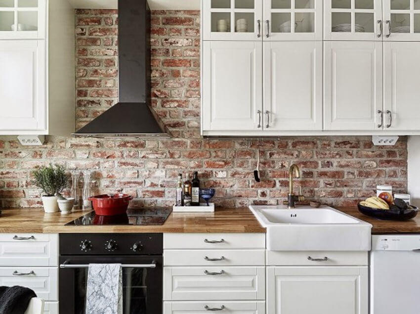 This rustic kitchen with an exposed brick backsplash is gorgeous!