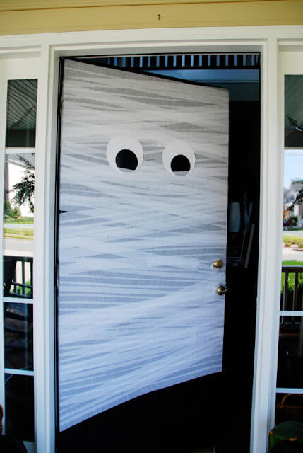Welcome trick-or-treaters to your home by wrapping your front door in white crepe paper streamers and turning it into a mummy!