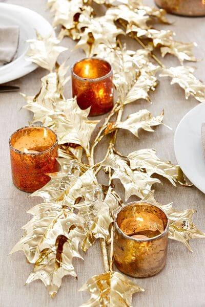 Spray paint leaves and arrange them in the center of your table with some candles and other fall-related decorations.