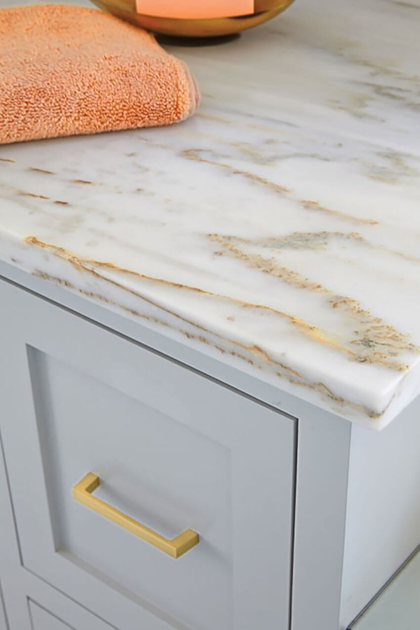 Gold accents in the marble pairs perfectly with the brass hardware.