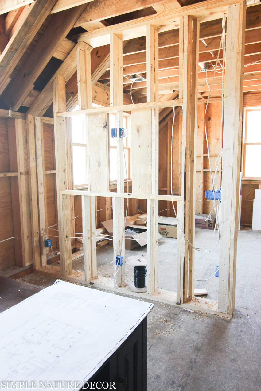 The framing for the divider wall has a space for a built-in TV.