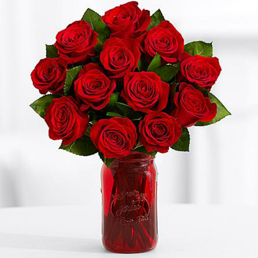 A dozen roses and put in a mason jar make a stylish gift. Let the guests take home the decoration! Image Source: Gifts.com