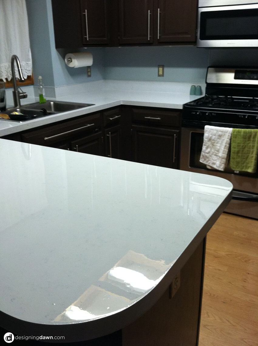 The contrast of the white countertop goes well with the dark cabinets.