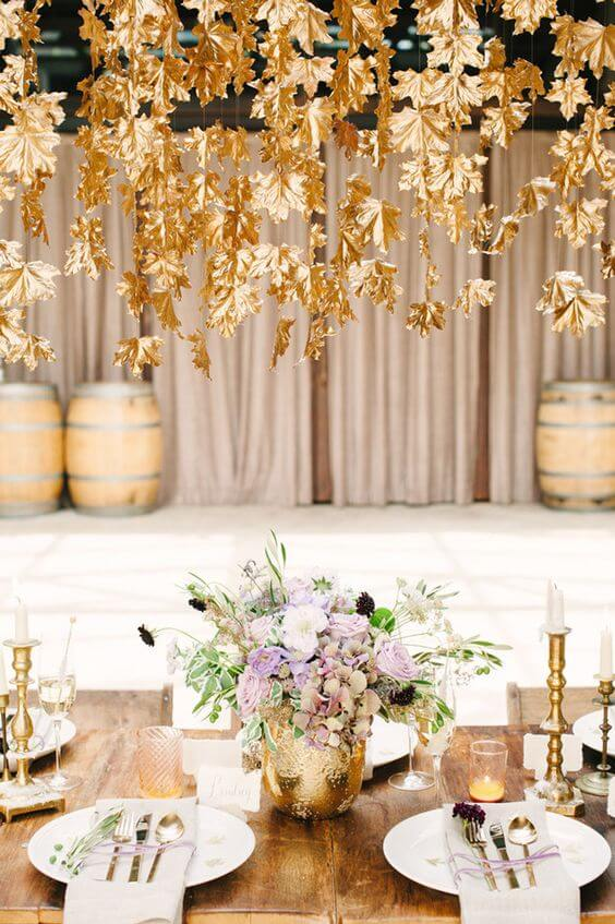 To take your Thanksgiving decorations to the next level, hang gold spray painted leaves from the ceiling to create an unforgettable atmosphere.