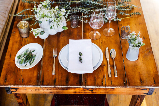 For a chic and simple tablescape, opt for all white plateware, silverware, and decorations.