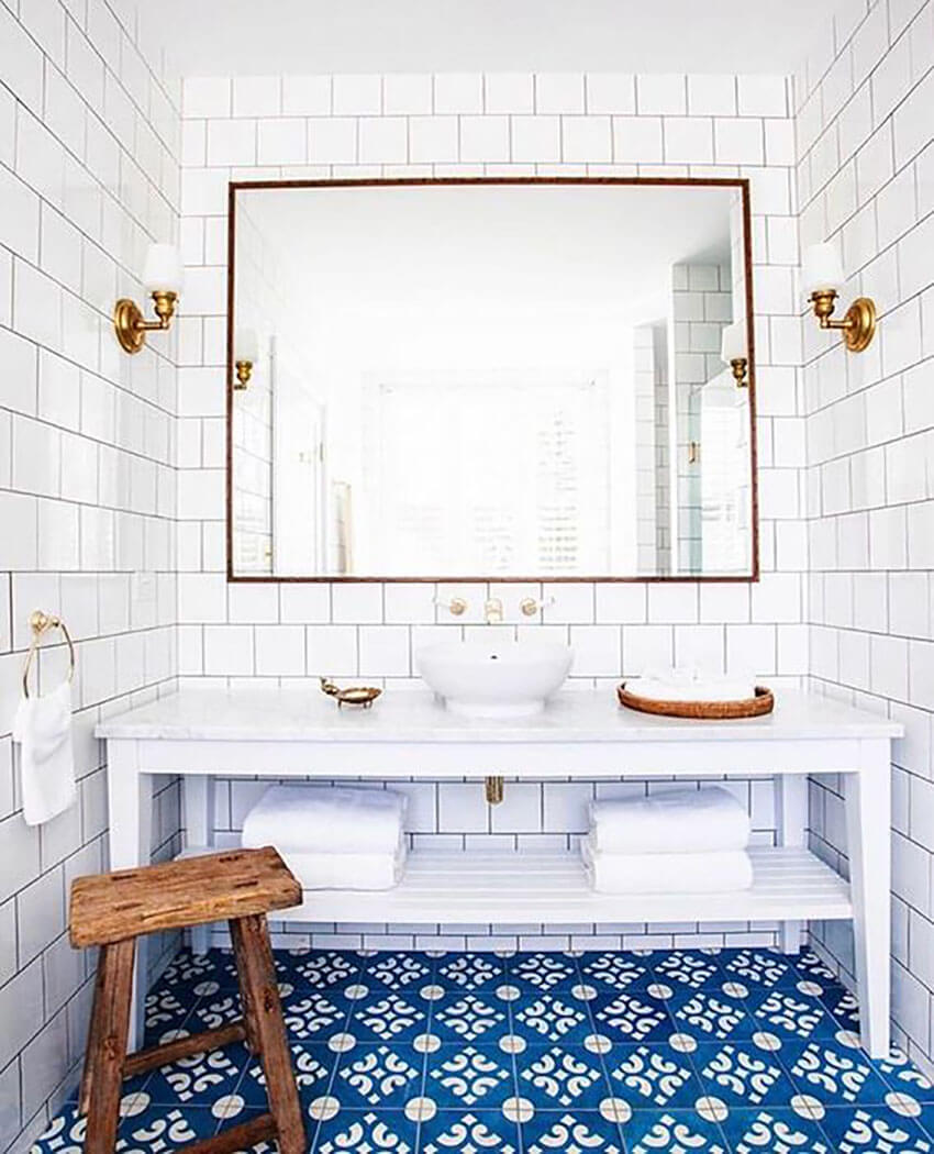 The mix of neutral tiling with colorful patterned floor creates an interesting visual effect.