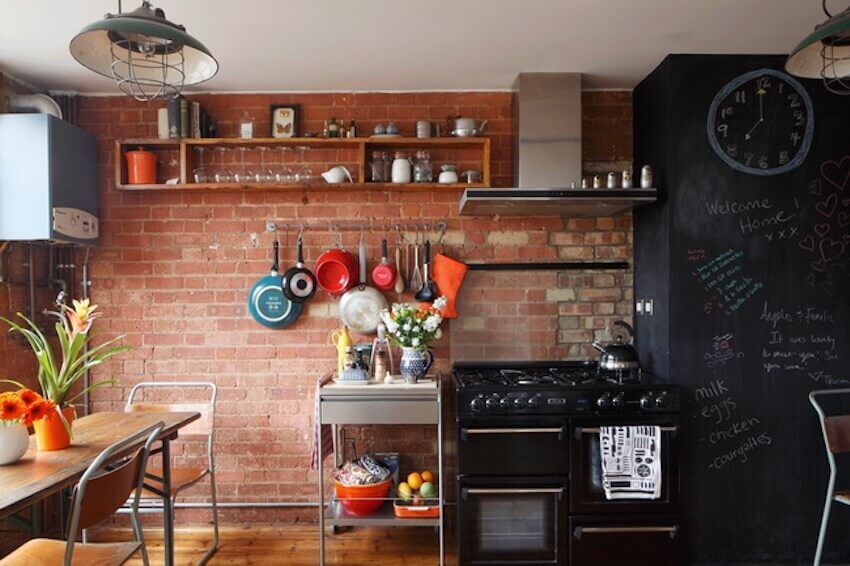Kitchen with exposed brick and chalkboard walls
