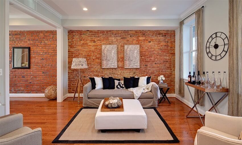White living room with exposed brick walls