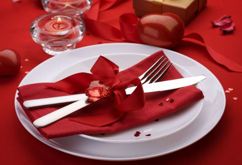 Napkins wrapped with red ribbons are very simple to make and add a delicate touch to the decor. Image Source: Buzz In Town