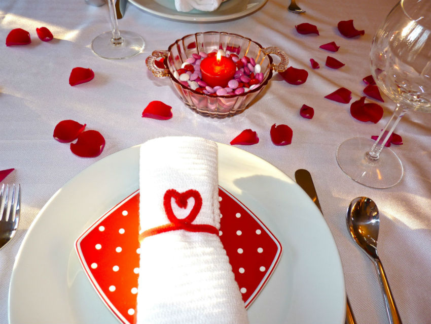 Soft petals scattered on the table are a great way to add romance to the table. Image Source: Girls On It
