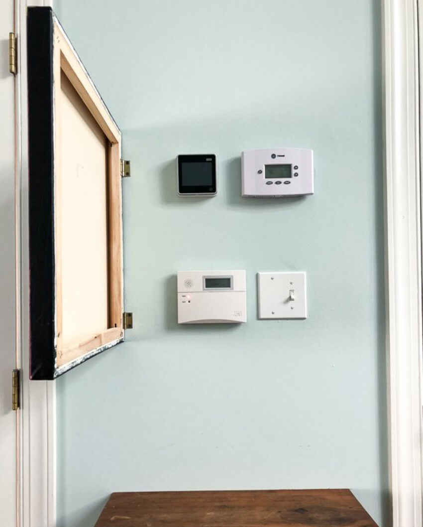 Install a painting on the wall to cover the thermostat controls.