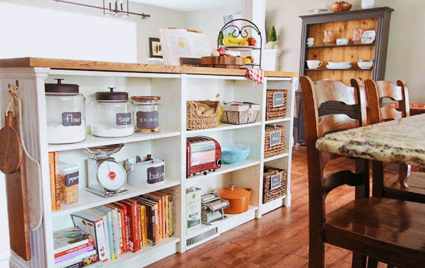A kitchen counter made out of bookshelves and a butche block!