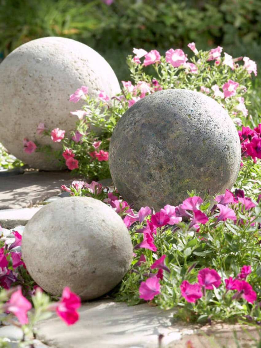 Concrete spheres are unique and gorgeous when combined with some flowers.