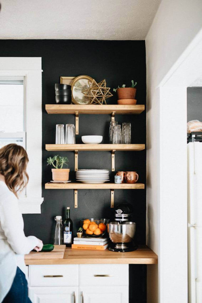 A modern kitchen with black walls and floating shelves!