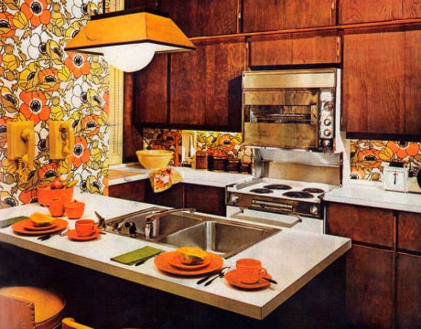 The acid orang utensils combined with the bright, floral wallpaper is so 1960s!