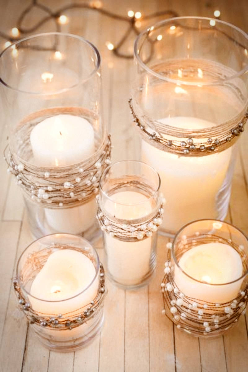 A glass candle holder with mercury garlands.