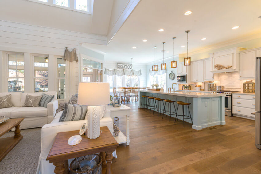This open floor shows a kitchen, living room, and dining room.